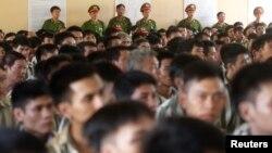 Cảnh sát đứng canh gác trong lúc các tù nhân chờ đợi trước khi được trả tự do từ nhà tù Hoàng Tiến, khoảng 100 km bên ngoài Hà Nội (ảnh Reuters, chụp ngày 30/8/2013).