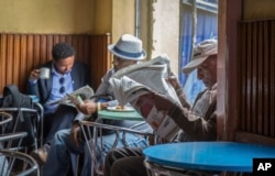 FILE - Ethiopian men read newspapers and drink coffee at a cafe in Addis Ababa, Ethiopia, Oct. 10, 2016. The Ethiopian government temporarily cut off internet access nationwide in early June, saying it was necessary to prevent students from cheating on final exams.