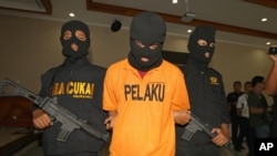 FILE - А suspected drug smuggler, his face obscured with a mask, is escorted by Indonesian Customs officers in Bali, Indonesia, Apr. 27, 2016.