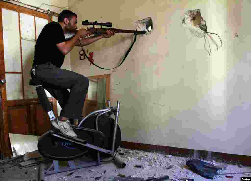 A Free Syrian Army fighter takes a position as he aims his weapon at the Justice Palace, which is controlled by forces loyal to Syria's President Bashar al-Assad, in Aleppo.