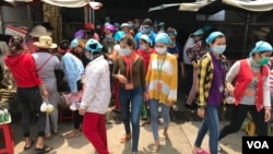 Garment workers leave the Propitious (Cambodia) Garment Ltd. factory for a lunch break in Kandal province, Cambodia, March 20, 2020. (Kann Vicheika/VOA Khmer)