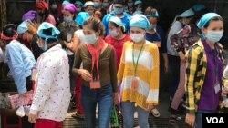 រូបឯកសារ៖ កម្មកររោងចក្រកាត់ដេរប្រភឹសឹស ខេមបូឌា ហ្គាមេន អិលធីឌី ក្នុងខេត្តកណ្តាល ចាប់ផ្តើមចេញពីរោងចក្រដើម្បីទទួលទានបាយថ្ងៃត្រង់ ដោយមានពាក់ម៉ាសគ្រប់គ្នា នៅថ្ងៃទី២០ ខែមីនា ឆ្នាំ២០២០។ (កាន់ វិច្ឆិកា/VOA Khmer)
