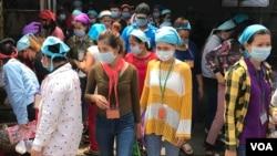 កម្មកររោងចក្រកាត់ដេរប្រភឹសឹស ខេមបូឌា ហ្គាមេន អិលធីឌី ក្នុងខេត្តកណ្តាល ចាប់ផ្តើមចេញពីរោងចក្រដើម្បីទទួលទានបាយថ្ងៃត្រង់ ដោយមានពាក់ម៉ាសគ្រប់គ្នា នៅថ្ងៃទី២០ ខែមីនា ឆ្នាំ២០២០។ (កាន់ វិច្ឆិកា/VOA Khmer)