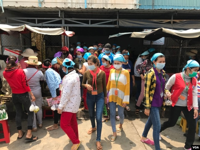 Garment factory workers wear face masks while on a lunch break near Propitious (Cambodia) Garment Ltd factory, in Kandal province, Cambodia, March 20, 2020. (Kann Vicheika/VOA Khmer)