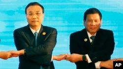 FILE - In this Sept. 7, 2016, photo, Chinese Premier Li Keqiang (L) and Philippine President Rodrigo Duterte link arms during the ASEAN Plus Three summit in Vientiane, Laos. After lashing out at longtime ally America, Duterte is making a state visit to Ch