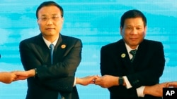 FILE - In this Sept. 7, 2016, photo, Chinese Premier Li Keqiang (L) and Philippine President Rodrigo Duterte link arms during an ASEAN summit in Vientiane, Laos. After lashing out at longtime ally America, Duterte is making a state visit to China in an apparent charm offensive.