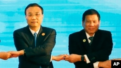 In this Sept. 7, 2016, photo, Chinese Premier Li Keqiang (L) and Philippine President Rodrigo Duterte link arms during the ASEAN Plus Three summit in Vientiane, Laos. After lashing out at longtime ally America, Duterte is making a state visit to Ch