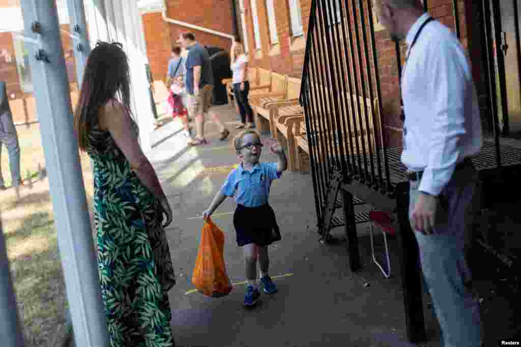 A student waves to his teachers as he arrives at St Dunstan's College junior school, as some schools re-open following the outbreak of COVID-19, in London, Britain.
