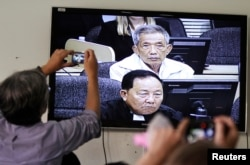 FILE - Journalists take photographs of a television screen showing the trial of Kaing Guek Eav, alias Duch, former chief of the S-21 prison, at the Extraordinary Chambers in the Courts of Cambodia (ECCC) on the outskirts of Phnom Penh, Feb. 3, 2012.