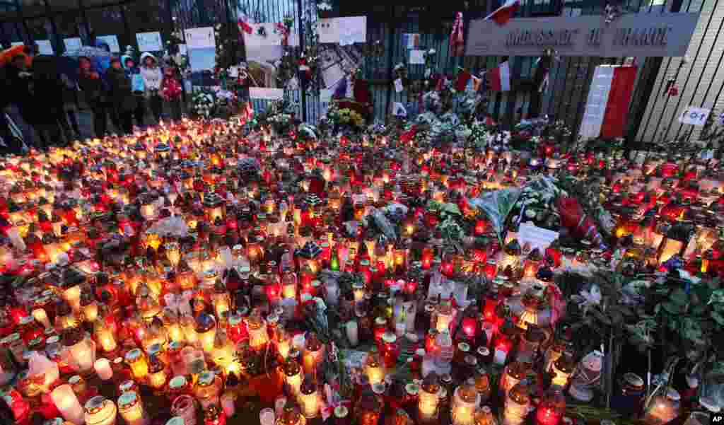 People place flowers and light candles for the victims of the deadly attacks in Paris, outside the French Embassy in Warsaw, Poland, Nov. 15, 2015.