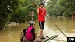 Cư dân ở Minh Hóa, tỉnh Quảng Bình chèo bè băng qua con đường bị ngập vì lũ lụt, ngày 6/10/2010