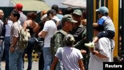 Soldados venezolanos resguardan la entrada de un supermercado en Caracas, mientras la gente hace fila para comprar productos básicos.