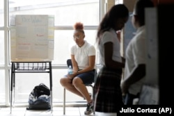 Tinazsha Johnson, 15, waits to talk about her project during the science fair a New Song Community Learning Center in Baltimore. Where she learned to cope with stress and sorrow.