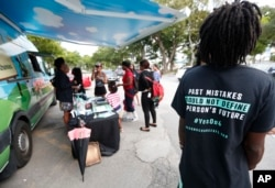 """People gather around the Ben & Jerry's """"Yes on 4"""" truck as they learn about Amendment 4 and eat free ice cream at Charles Hadley Park in Miami, Oct. 22, 2018."""