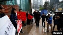 在加拿大不列顛哥倫比亞省一家正在審理孟晚舟案的法院外手舉中國國旗和標語牌的孟晚舟支持者。(2018年12月11日)