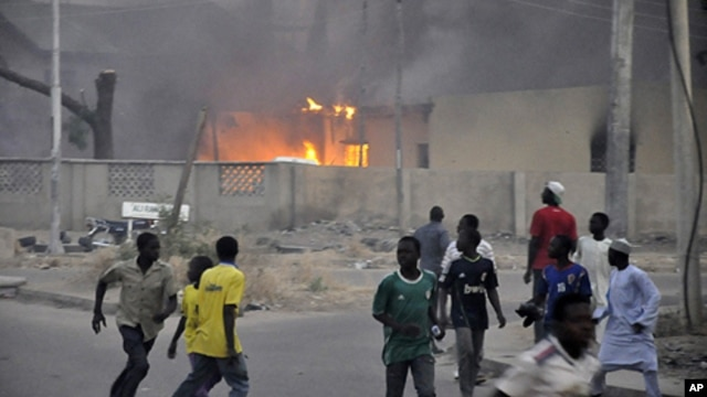 Smoke rises from police headquarters as people run for safety in Nigeria's northern city of Kano, Jan. 20, 2012.