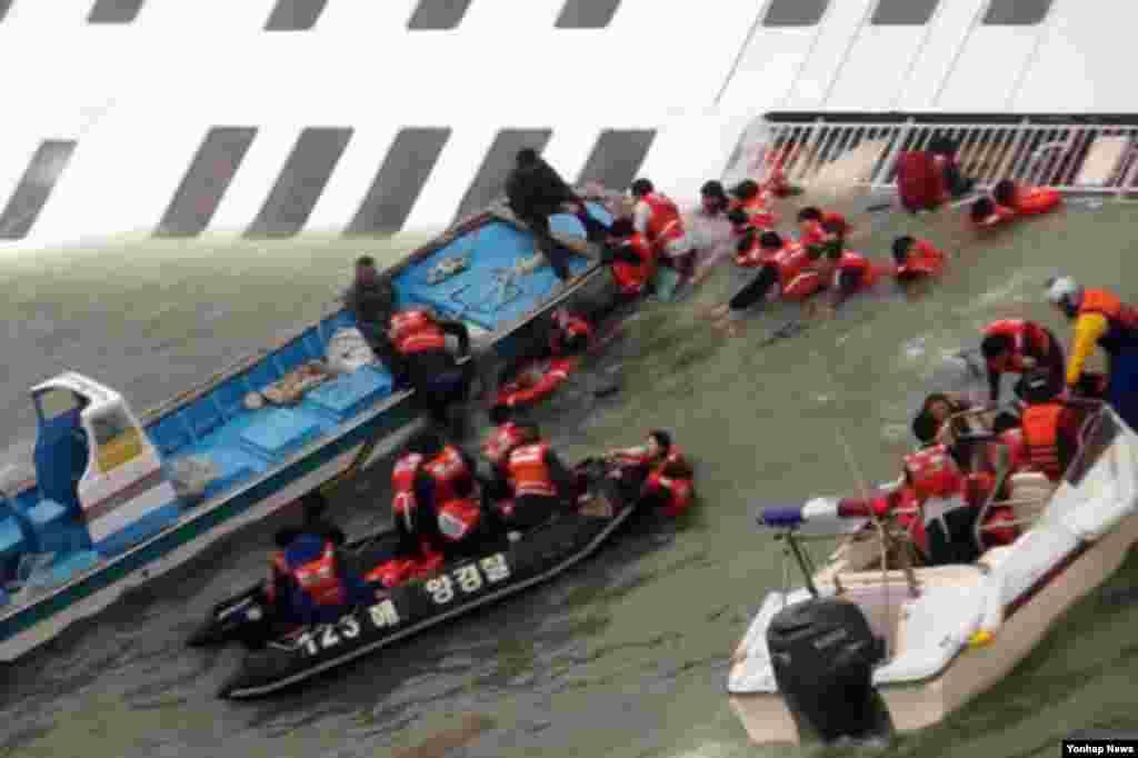 한국 목포해경 대원들이 16일 전남 진도 해역에서 세월호 침몰 직전 승객을 구조하고 있다.
