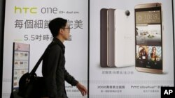 A man walks past an HTC smartphone billboard in Taipei, Taiwan, Sept. 21, 2015.