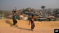 Rohingya refugees carry a hume pipe in Balukhali refugee camp near Cox's Bazar, in Bangladesh, Nov. 17, 2018.
