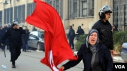 Seorang perempuan Tunisia mengibarkan bendera saat berdemonstrasi di menuntut peletakan jabatan para pejabat pemerintah yang loyal pada mantan Presiden Zine El Abidine Ben Ali.