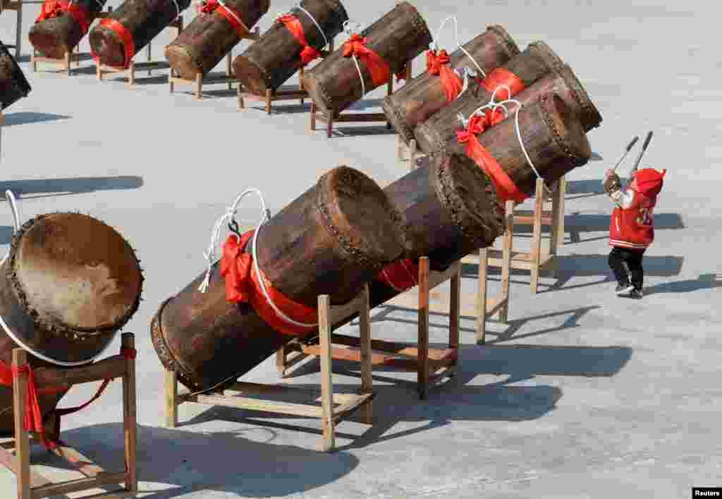 Criança brinca com tambores tradicionais da região autónoma chinesa de Miao, na província de Guizhou.
