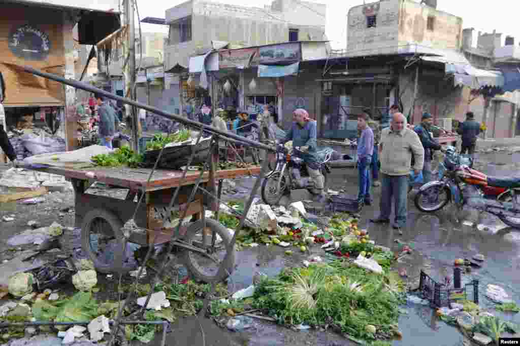 Residents inspect a site after it was hit by what activists said were air strikes by forces loyal to President Bashar al-Assad in Raqqa, Syria, Nov. 25, 2014.