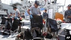 Thành viên trên tàu Hải quân Indonesia KRI Bung Tomo đứng cạnh các ghế máy bay trục vớt lên được từ biển Java.