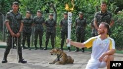 Seorang atlet memegang Obor Olimpiade di sebelah macan tutul dalam sebuah upacara di Manaus, Brazil utara (20/6).