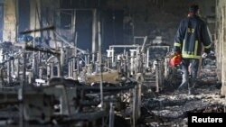 A firefighter inspects Tazreen Fashion factory in the Ashulia industrial belt of Dhaka, on the outskirts of Bangladesh's capital, after a fire swept through it, killing more than 100 people, November 25, 2012.