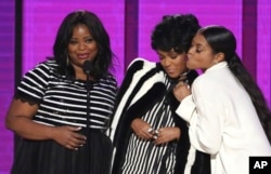 "FILE - Octavia Spencer, from left, Janelle Monae and Taraji P. Henson of the film ""Hidden Figures,"" present an award at the American Music Awards in Los Angeles, Nov. 20, 2016."