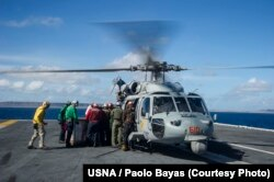 """Sailors aboard the U.S. Navy's forward-deployed aircraft carrier USS George Washington (CVN 73) load containers of water onto an MH-60S Seahawk from the """"Golden Falcons"""" of Helicopter Sea Combat Squadron (HSC) 12 in support of Operation Damayan, Nov. 15,"""