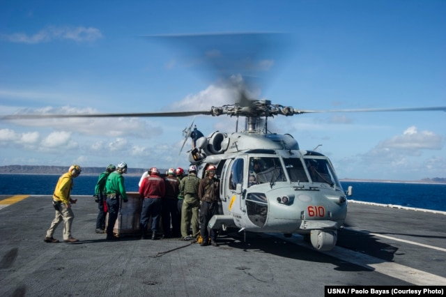 Sailors aboard the U.S. Navy's forward-deployed aircraft carrier USS George Washington (CVN 73) load containers of water onto an MH-60S Seahawk from the