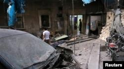 Petugas medis memeriksa kerusakan di luar sebuah rumah sakit lapangan setelah terjadinya serangan udara di kawasan al-Maadi yang dikuasai pemberontak di Aleppo, Suirah (28/9). (foto: REUTERS/Abdalrhman Ismail)