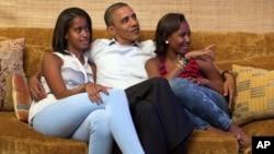 El presidente Obama y sus hijas Malia (izquierda) y Sasha, observan el discurso de la Primera Dama Michelle Obama.