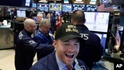 Pakar saham Frank Masiello mengenakan topi Dow Jones 20.000 saat bekerja di lantai Bursa Saham New York (NYSE), Rabu (25/1). Untuk pertama kalinya, indeks Dow Jones mencapai rekor tertinggi dengan pencapaian di atas 20.000.