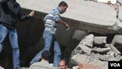 Warga Turki berusaha menyelamatkan beberapa orang yang masih terjebak di reruntuhan gedung, akibat gempa 7.2 skala Richter di Turki tenggara (23/12).