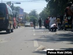 Polisi mensterilkan jalanan yang diduga terdapat serpihan tubuh korban ledakan bom di sekitar Gereja Katolik Santa Maria Tak Bercela di Surabaya, 13 Mei 2018. (Foto: VOA/Petrus Riski)