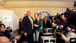 "Kandidat presiden dari koalisi ""Mimpi Georgia"" Georgy Margvelashvili dan putrinya di sebuah TPS di Tbilisi, Georgia, Minggu (27/10). (AP/Georgy Abdaladze)"