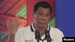Presiden Filipina Rodrigo Duterte mengacungkan jari tengah saat berbicara di depan para pejabat pemerintah di kota Davao, Filipina selatan (20/9). (Reuters/Lean Daval Jr)