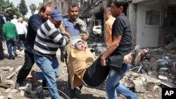 11일 시리아와 접경한 터키 남부 하타이주에서 차량폭탄 테러가 발생한 가운데 사람들이 한 여성 부상자를 나르고 있다.