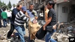 Para warga di Reyhanli dekat perbatasan Turki dengan Suriah mengangkat perempuan korban ledakan bom mobil, Sabtu (11/5). (AP/Anadolu Agency, Lale Koklu)