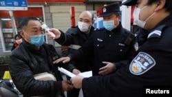 湖北武漢街頭設立的檢查卡社區工作人員檢測行人的體溫,警察檢查其身份文件。 (2020年2月20日)