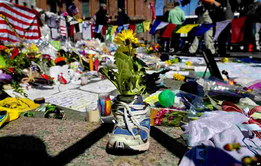 A memento of flowers in a running shoe rests at a makeshift memorial in Boston's Back Bay neighborhood, April 18, 2013, a few blocks from the finish line of the Boston Marathon.