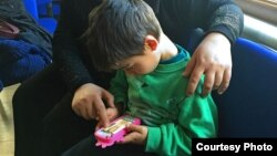 Mohammed, age 5, uses his mother's smartphone to play games earlier this year. Before his family fled from the Syrian city of Aleppo to Istanbul, Mohammed's grandfather was killed. (photo courtesy Liv Marte Nordhaug)