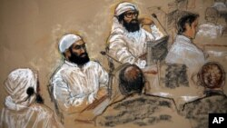 FILE - In this courtroom sketch, alleged 9/11 co-conspirators, left, sit with their legal teams during a hearing in the Camp Justice compound for the U.S. war crimes commission on Guantanamo Bay U.S. Naval Base in Cuba, July 16, 2009. Three of the five defendants in the case attended the hearing; from left, they are Walid Bin Attash, Ali Abdul Aziz Ali and Mustafa Ahmed al-Hawsawi.