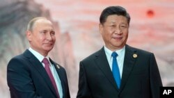FILE - Chinese President Xi Jinping, right, and Russian President Vladimir Putin pose for a photo at the Shanghai Cooperation Organization (SCO) Summit in Qingdao in eastern China's Shandong Province, June 10, 2018.