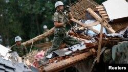 20일 일본 히로시마시에 내린 폭우로 산사태가 발생해 주택가가 붕괴된 가운데, 자위대원들이 잔해 속에서 생존자 수색에 나섰다.