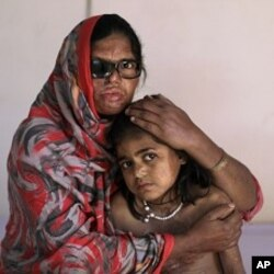 Pakistani acid attack survivor, Azim Mai, 35, holds her daughter Shaziya, 8, while sitting on a bed waiting to have a massage session for their wounds, at the Acid Survivors Foundation (ASF) in Islamabad, Pakistan, December 13, 2011.