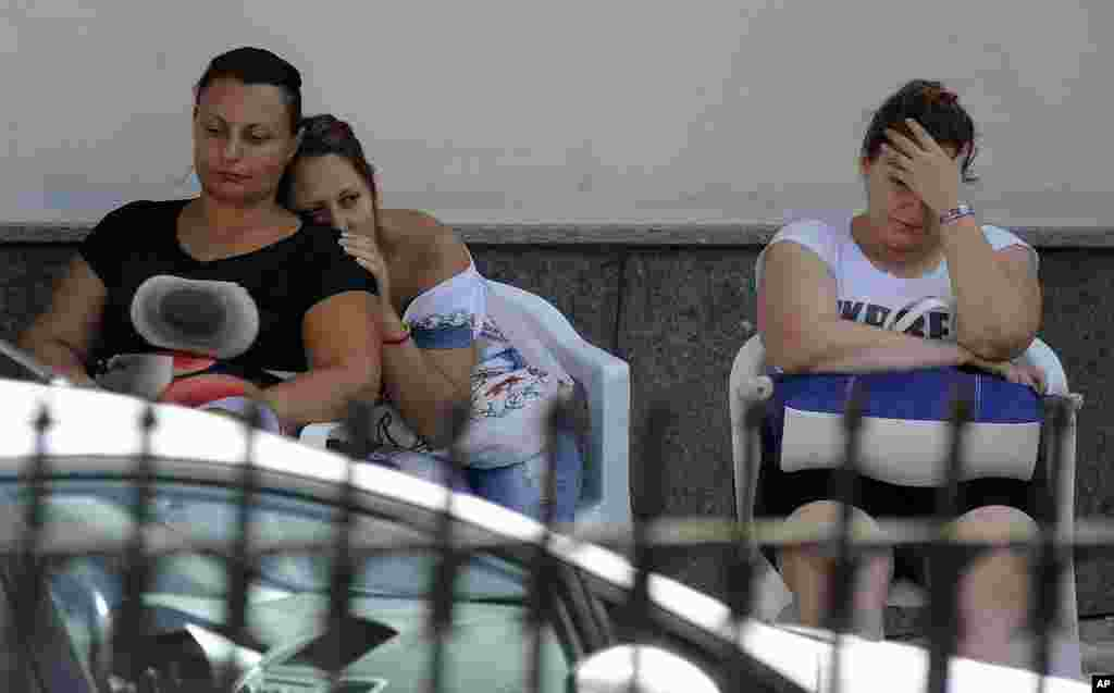 People comfort each other outside a gym facility of an elementary school turned into a morgue, in Monteforte Irpino, southern Italy. An Italian tour bus crashed through a wall of a highway bridge and plunged some 30 meters (100 feet) into a wooded ravine, killing at least 38 people Sunday night.