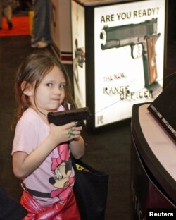 A young attendee tries out a pistol during the National Rifle Association's (NRA) 141st Annual Meetings & Exhibits in St. Louis, Missouri, April 13, 2012.